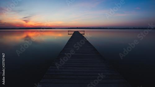 Aluminium Pier Old empty wooden jetty on lake, during sunrise.