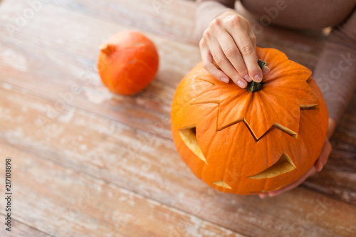 Foto Murales halloween, decoration and holidays concept - close up of woman with carved pumpkin or jack-o-lantern at home