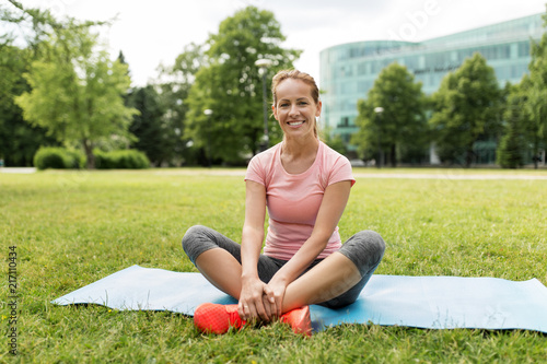 Poster fitness, sport and healthy lifestyle concept - smiling woman sitting on exercise mat at park