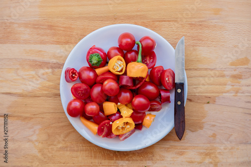 Foto Spatwand Hot chili peppers Knife and tomatoes in plate on wooden table. Above view