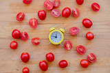 little alarm clock and tomatoes on wooden table. Above view