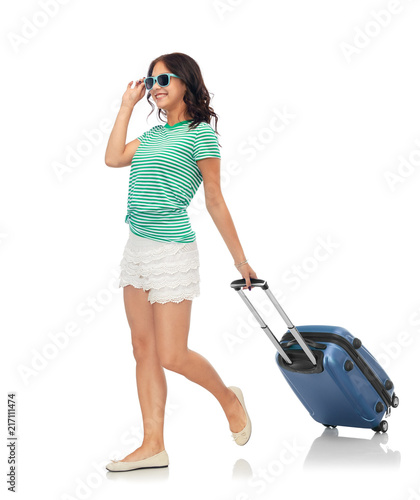 Foto Murales tourism, summer holidays and vacation concept - happy teenage girl in sunglasses with travel bag over white background