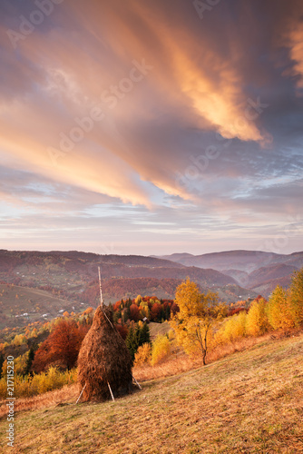 Autumn landscape with a haystack in the mountains - 217115230