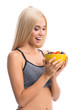 Woman in sportswear with plate of fruits, isolated