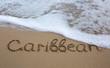 Quadro Word Caribbean written on the sand near the sea.