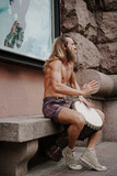 A street musician plays the drum. Charismatic hippies in the center of the city. The drummer plays African motifs.