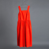 red fashionable dress hanging on a hanger on a gray background, concept of shopping and fashion