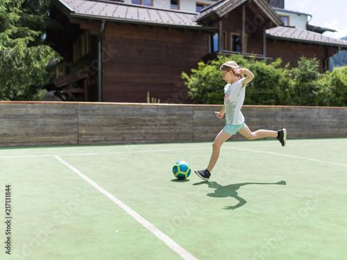 Fotobehang Voetbal Ein 9 jähriges Mädchen trainiert ihre Schußtechnik mit einem Fußball uf dem Fußballplatz