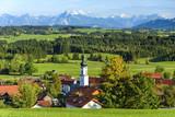 idyllisch gelegenes Dorf vor der Kulisse der bayrischen Alpen - 217140826