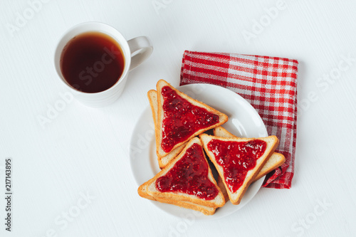 Foto Murales Toast with raspberry jam and a mug of tea on a white background