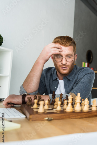 Foto Murales handsome pensive man looking at chessboard at home