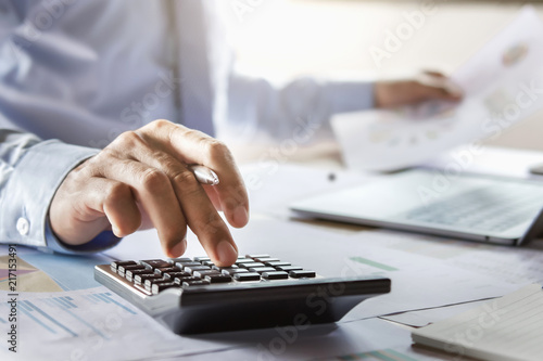 Fridge magnet accountant working on desk using calculator for calculate finance report in office