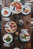 top view of various tasty italian dishes and drinks on wooden rustic table at restaurant