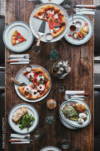 Foto Murales top view of various tasty italian dishes and drinks on wooden rustic table at restaurant