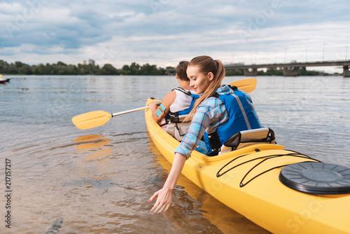 Ręka w wodzie. Blondynki kobieta stawia jej rękę w wodzie podczas gdy kayaking z jej chłopakiem