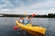 Couple of sportsmen. Couple of young active sportsmen wearing life vest feeling relaxed while kayaking together