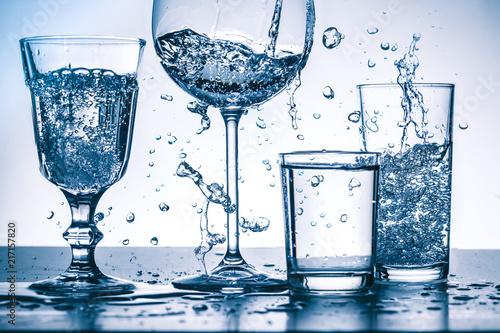 Foto Murales Viele Wasserspritzer mit Gläsern auf hellem  Hintergrund