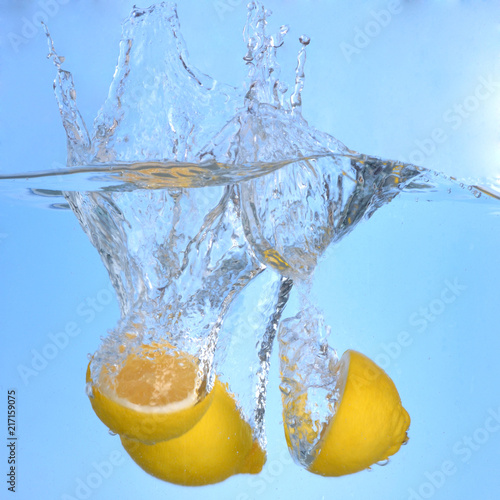 Foto Murales Tropical fruits fall deeply under water with a big splash lemon drop into water splashing on blue backgfround