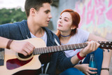 Beautiful music. Nice young man singing a song while being together with his girlfriend