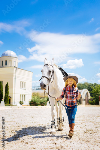 Leading horse. Amused blonde-haired schoolgirl wearing cowboy hat leading white horse on race track