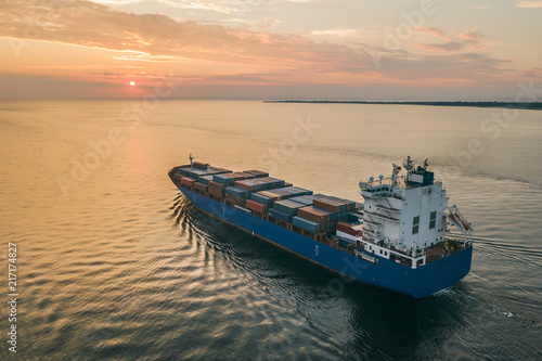 Canvas Zeilen Aerial view of container ship sailing in sea at sunset