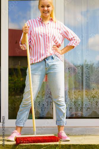 Foto Murales Woman using broom to clean up backyard patio