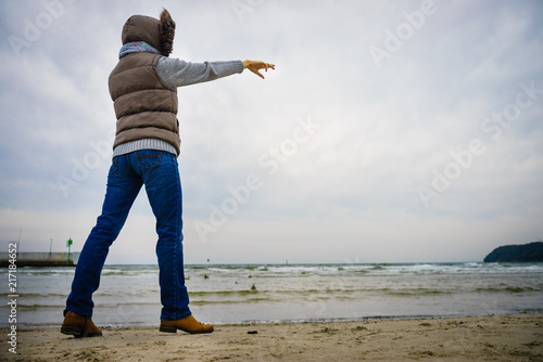 Foto Murales Woman walking on beach, autumn cold day