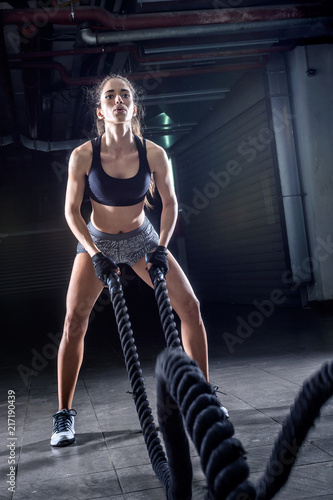 Foto Murales Battle ropes session. Attractive young fit and toned sportswoman working out in fitness  training gym
