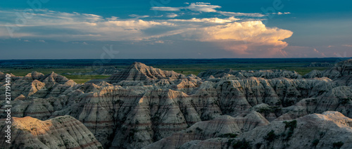 Sunset over Badlands National Park with thunderhead in the background - 217191410