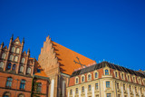 old medieval city district with church colorful houses and narrow street in bright summer day time