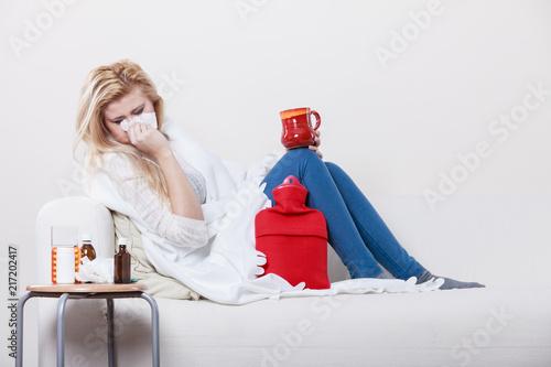 Foto Murales Woman being sick having flu lying on sofa