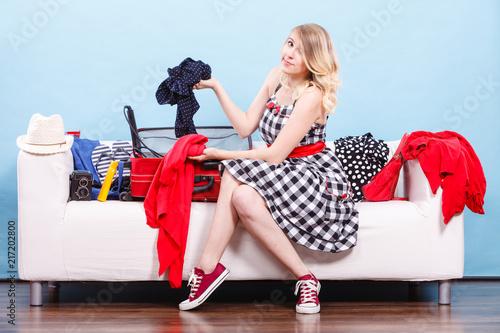 Foto Murales Woman choosing things to pack into suitcase