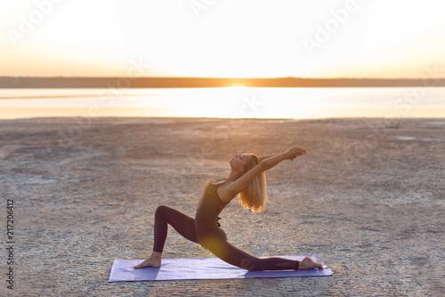 Obraz na płótnie Girl practicing yoga poses at sunrise. Virabhadrasana pose.