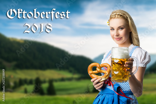 Leinwanddruck Bild attraktive junge Frau im Dirndl vor Alpenlandschaft