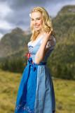 unge Frau im Dirndl schaut auf Alpenlandschaft