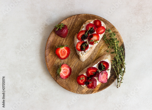 Bruschetta or sandwich with strawberries, cream cheese or ricotta, balsamic vinegar and thyme on a light background. Summer snack food. Italian breakfast. Italian cuisine.