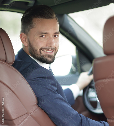 Leinwanddruck Bild businessman sitting at the wheel of a car and looking at the camera