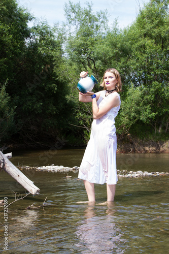 Foto Murales Girl with a jug in the water