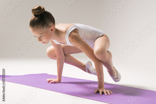 Plakat A young gymnast is doing an exercise. Meditation. Child. Children's yoga. Girl in a white swimsuit. Children's sport. Children's gymnastics