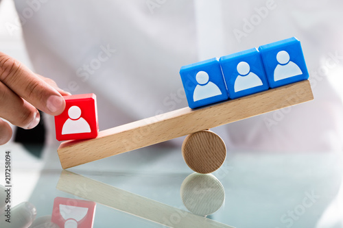 Person showing unbalance between single red and blue blocks