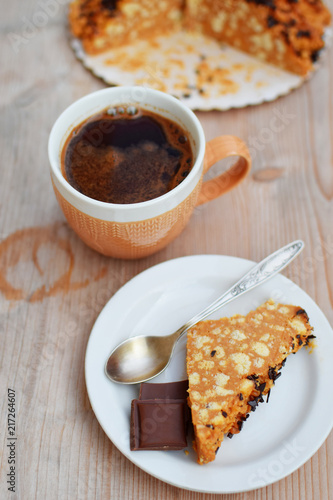 Wall mural Piece of cake and chocolate on white plate with spoon and cup of coffee on natural wooden table vintage tone at shallow depth of field.