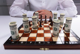 Businessman Playing Chess With Chess Piece And Banknotes