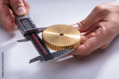 Person Measuring Gear's Size With Digital Caliper