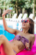 Selfie time. Slim famous model making selfie while relaxing in the pool lying on bright pink air mattress