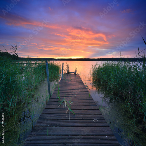 Aluminium Pier Dramatic Sunset over Lake with wooden Pier and Reeds