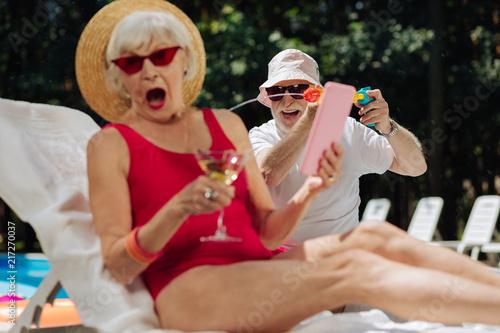 Śmiejący się człowiek. Śmiejąc się człowiek sobie ciemne okulary zraszanie wodą na jego zaskoczony modne żony