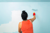 Woman at painting a room with paint roller - 217275458