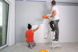 Couple painting a room with paint rollers - 217275495