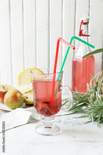 Aluminium Sap Cup of summer plum lemonade with straws. Decor of a green flower. Rustic. White wooden background.