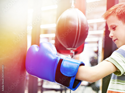 Boy in boxing glove and punching bag